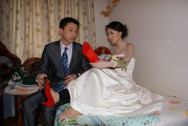 新娘遭醉酒好��o._新郎给新娘穿鞋,中间俩人不知道还在交流什么.