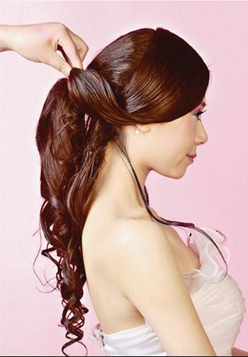 b:使用卷发棒,将头发用内扣和外翻的手法交替电卷头